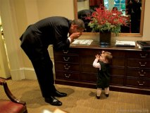 President Barack Obama plays with the daughter of Emmett Beliveau, the director of advance, in the Outer Oval Office, Oct. 30, 2009.