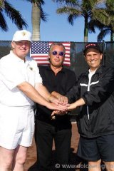 Donald J. Trump, Jim Williams (President of Williams TeleCommunications Corp.) and Mike Milken smiling with hands in a pile in front of the US FLAG.