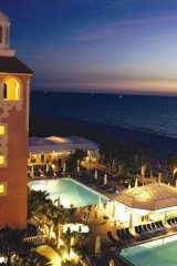 Night view of the pool and ocean at the Don Cesar Hotel.