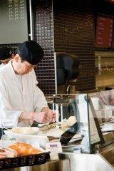 Japanese sushi chef prepares fresh sushi inside mcewan.