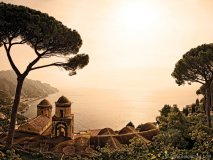 An orange glow cascades across Chiesa dell'Annunziata and the Amalfi Coast, seen from the Villa Rufolo Garden. Photo by Robert Leon
