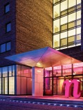 "A warm pink glow accents the oversized pink ""n"" that welcomes guests at the entrance of the Nhow Hotel. Photography by Lukas Roth"