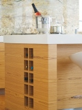 A wine rack has been incorporated into the end of this teak kitchen island.