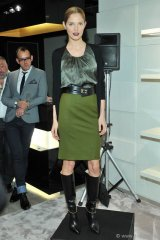 Model wears a green wool skirt paired with a snake-patterned silk shell under a black cashmere cardigan. This Boss Black ensemble is polished off with black knee-high chain boots and belt, Photos By George Pimentel/WireImage