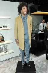 Model in a camel-coloured coat over a grey knit shirt and tie with a light grey flannel trouser and brown loafers, all from the Boss Black collection, Photos By George Pimentel/WireImage