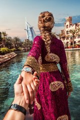 The Burj Al Arab Jumeirah looks on in the distance as Nataly leads Murad through the vibrant city of Dubai