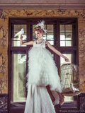 Dress by Anna Kania Couture; pearl necklace by Galerie Pearls Collection by Karin van Noort; feather headpiece by Honeymoon