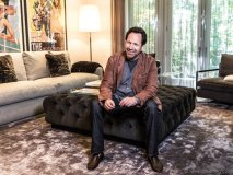 Barry Avrich in the living room of his Toronto home, wearing a suede jacket by Brunello Cucinelli, a Jil Sander cardigan, a John Varvatos T-shirt and denim from AG Jeans, all courtesy of Harry Rosen