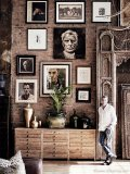 The feature wall of the living room is dominated by portraits Button has painted since picking up painting again a couple of years ago