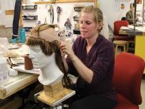A hair wig stylist focuses on the job ahead.