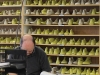 A wall of shoe moulds set the backdrop for a soulful artisan hard at work.