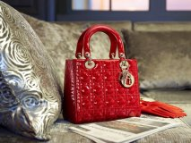 A red Lady Dior handbag with matching gloves