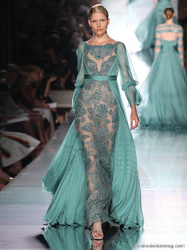 Awash with transparent feminine elegance, this sea green gown oscillates with lace, sequins and light embroideries.