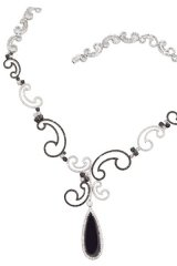 Dipping seductively into womanly curves, this white gold necklace weds onyx with black and white diamonds (707 of them!) for a mysterious trail of luxury.