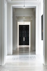 Reflecting the pristine and stately feel of an art gallery, this seemingly endless hallway features slab marble floors and a stone mirror frame that holds an antique-cut mirror wall