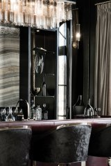 This luxurious great-room bar boasts a slab onyx back wall with a leather-wrapped, plum-coloured bar and sculpted glass lighting