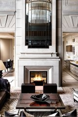 Sumptuous and inviting, this great room features 25-foot ceilings and walls layered with fine materials, custom-designed bronze screens and floors in cut slab marble