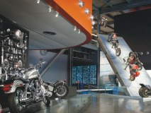 A varied collection of bikes flies off a large ramp at one of the museum's many exhibits.