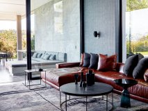 The home's cinema lounge, which opens onto a covered patio, is made intimate and cosy with grass cloth wallpaper and a Paco rug. The Calvinia coffee table and Cube side table are by Tonic Design
