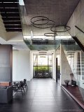 As you enter the house a powerful and arresting space opens up to a triple-volume, seven-metre-high living area framed on either side by walnut-clad floating staircases with frameless glass balustrades
