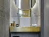 """The vanity in the guest bathroom is a prime example of the way in which Enrico Daffonchio and Frances Joynt have layered and contrasted raw materials. """"When you have a mirror and brass over the raw concrete, there's such a strong tension between the materials,"""" says Daffonchio"""