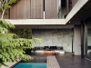 The patio extends seamlessly out from the living area, paved with the same large ceramic tiles used throughout the house. While the pool appears large, its size is exaggerated by the beach entry, which slopes gradually into the water