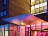 """A warm pink glow accents the oversized pink """"n"""" that welcomes guests at the entrance of the Nhow Hotel. Photography by Lukas Roth"""