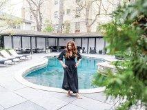 koifman poses in a black caftan by her backyard pool