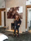"""Natasha Koifman stands in front of the fireplace in her master bedroom; the photo  by Roberto Dutesco is from  his collection """"The Wild  Horses of Sable Island"""""""
