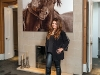 "Natasha Koifman stands in front of the fireplace in her master bedroom; the photo  by Roberto Dutesco is from  his collection ""The Wild  Horses of Sable Island"""