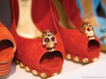 Alexander McQueen's skull-embellished red suede pumps with gold studs can't sit still on her shelves