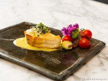 Chilean sea bass on corn sauce with purple kale guanciale and cherry tomatoes