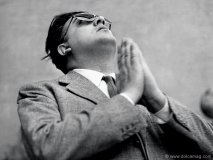Federico Fellini stands in a prayer-like pose looking towards the heavens. Private Collection