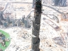 The Burj Dubai – supported by its flower-like base – makes neighbouring 50-storey buildings look like bits of debris, scattered along a seemingly barren landscape.