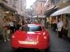 A Ferrari 599 GTB Fiorano zips through a narrow street near Lake Maggiore.