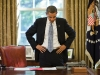 President Barack Obama reads a document during a break between phone calls in the Oval Office, Oct. 13, 2009.