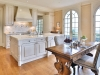The kitchen features custom built-in millwork and decorative glass display shelving