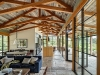 Tehama 2: The interior concrete flooring extends to the exterior porch, while the ceiling is paneled in reclaimed barn-wood siding and the asymmetrical trusses are Douglas fir. The result is a low-maintenance home that doesn't require the need for air conditioning | Photo credit: Tim Griffith Photography