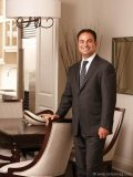 Sam Mizrahi makes himself the centrepiece in Lytton Park Townhomes' model suite dining room.