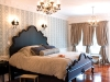 Much like Marie Antoinette's bed chamber, these private quarters are adorned with planked flooring, flourishing drapery, and European light fixtures. An abundance of silk pillows complement the lush bedding, accentuated by a hand-carved headboard.