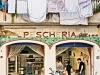 Pescheria (fish shop) and Italian woman in window, Amalfi Village. Photo by Robert Leon