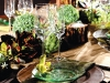 This rustic arrangement is given a modern twist as pronounced candles and an assortment of foliage complement slender stemware and transparent plates.