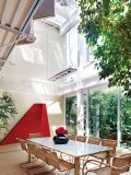 An open-concept atrium with skylight and large windows brightens the dining area and increases intimacy with nature